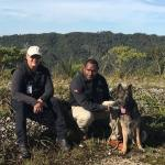 Scott in Papua New Guinea highlands with dog and handler